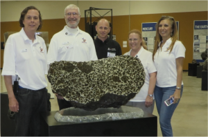 OSIRIS-REx Ambassadors Bliss, Jack Monahans, Alan Strauss (also Director of the Mt. Lemmon SkyCenter), Dolores Hill and LuAnn Kidd surround the famous Fukang pallasite meteorite during the International Meteorite Collectors Meeting at the OSIRIS-REx Mission Operation Center. (The spectacular meteorite is owned by Marvin Killgore).  Photo by Rik Hill.