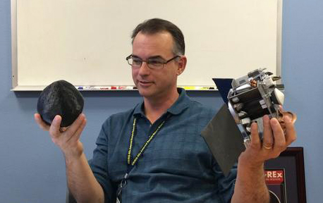 OSIRIS-REx's Principal Investigator, Dante Lauretta, holding a model of the OSIRIS-REx spacecraft.
