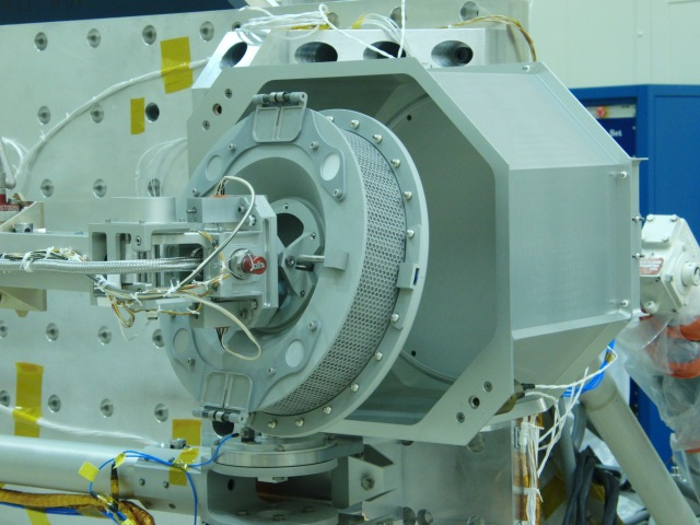 The sample head at the end of the TAGSAM mechanism is being inserted into the fixture it will reside in during the vibration testing. Image Credit: Lockheed Martin
