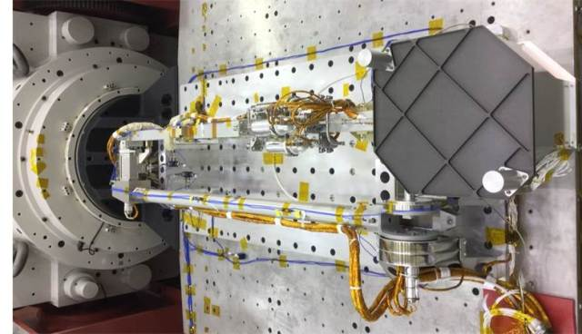 The TAGSAM arm and sample container (inside the dark grey enclosure) undergoing vibration testing. Image Credit: Lockheed Martin
