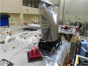 The OTES instrument installed on the science deck of OSIRIS-REx. The optics are protected by a mylar cover to prevent contamination during ATLO processing.